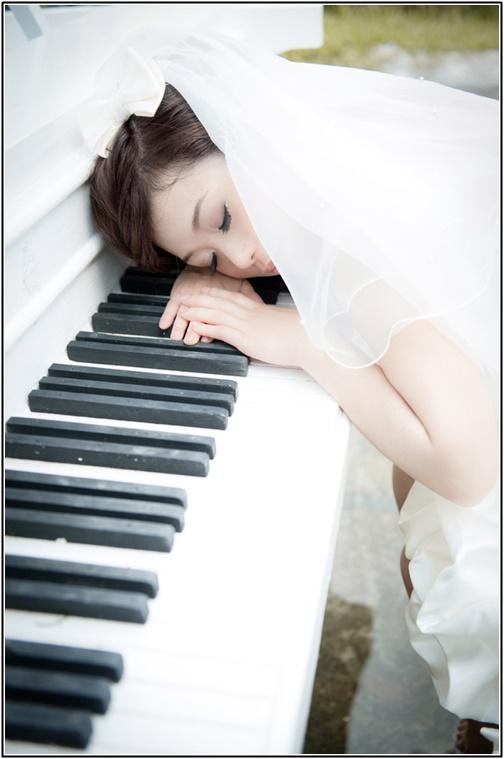 ピアノの上で寝るウエディングドレス姿の女性の画像