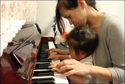 女のピアノの先生が小さな子供に教えている画像