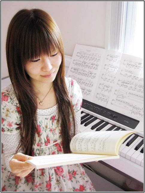 ピアノの楽譜を見る女性の画像