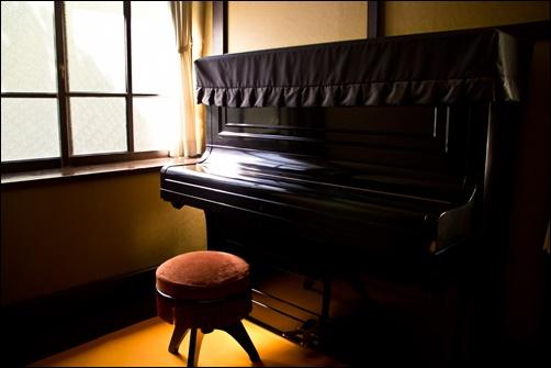 アップライトピアノと椅子の画像