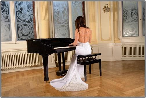 ウエディングドレス姿でピアノ演奏する女性の画像