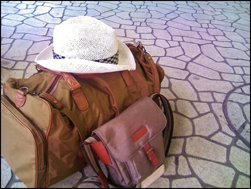 道路に置かれた茶色の旅行バックに白い帽子の画像