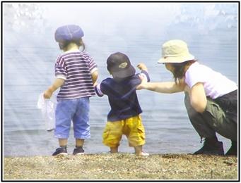 浜辺で兄弟が遊ぶのをお母さんが隣で声を掛けている画像