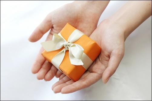 オレンジのプレゼントBOXを差し出す女性の画像
