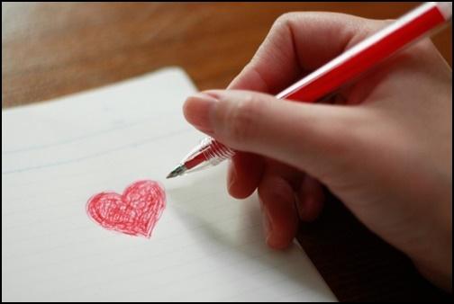 赤ボールペンで赤いハートをノートに書いた画像