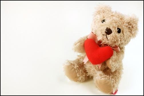熊の人形が赤いハートを持っている画像