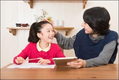 女の子の子供を褒める母親の画像