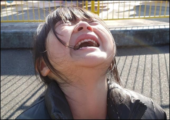 女の子が上を向いて泣いている画像